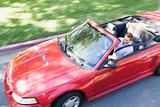 Man driving convertible car smiling