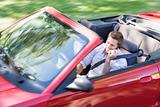 Man driving convertible car using cellular phone and smiling