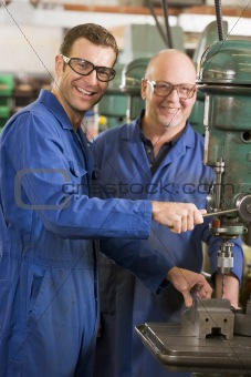 Two machinists working on machine