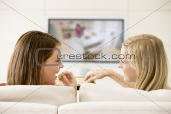 Two women in living room watching television eating chocolates s