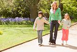 Mother and two young children walking on path holding hands smil