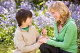 Mother and son outdoors holding flowers smiling