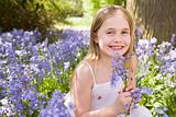 Young girl outdoors holding flowers smiling