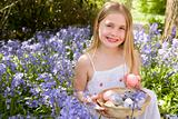Young girl outdoors holding various eggs in basket smiling