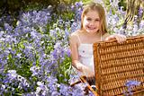 Young girl sitting outdoors with picnic basket smiling