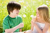 Two young children sitting outdoors holding dandelion heads smil