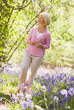 Woman walking outdoors holding flower smiling