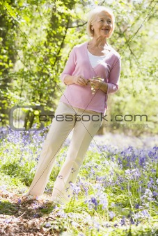 Woman standing outdoors holding flower smiling