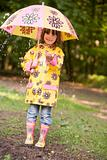 Young girl outdoors in rain with umbrella smiling