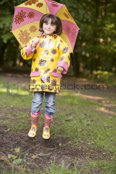 Young girl outdoors with umbrella jumping and smiling
