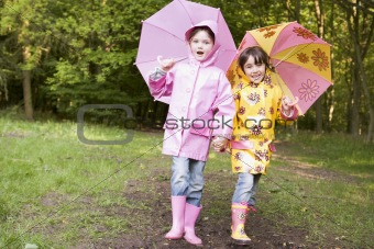 Two sisters outdoors with umbrellas smiling