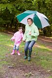 Father and daughter outdoors with umbrella smiling