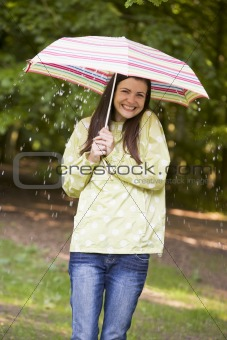 Woman outdoors in rain with umbrella smiling