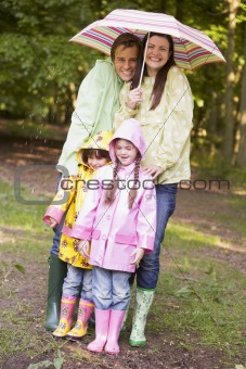Family outdoors in rain with umbrella smiling