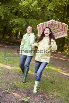 Couple outdoors running with umbrella smiling