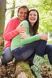 Couple outdoors in woods sitting on log smiling