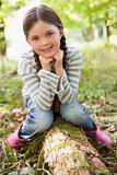 Young girl outdoors in woods sitting on log smiling