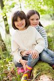 Two sisters outdoors in woods sitting on log smiling