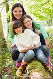 Mother and daughters outdoors in woods sitting on log smiling