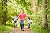 Father and daughters walking on path holding hands smiling