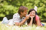 Couple lying outdoors with flower smiling