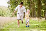Father and son running on path smiling