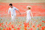 Couple walking in poppy field holding hands smiling