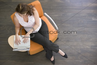 Businesswoman sitting indoors with laptop