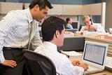Two businessmen in cubicle looking at laptop