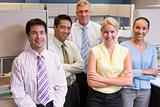 Business team standing in cubicle smiling