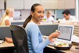 Businesswoman in cubicle with laptop eating salad