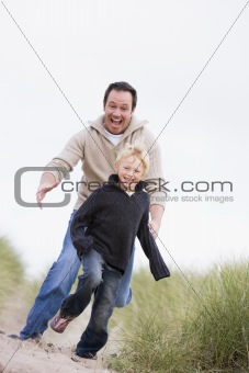 Father and son running on beach smiling