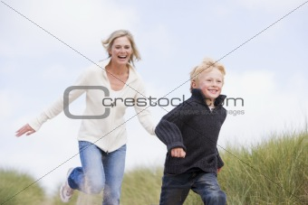 Mother and son running on beach smiling