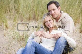 Couple sitting on beach smiling