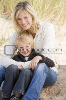 Mother and son sitting on beach smiling