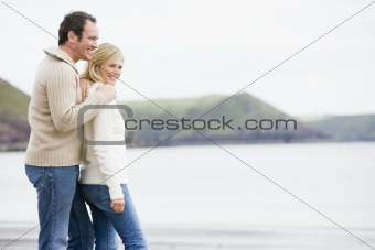 Couple standing on beach smiling