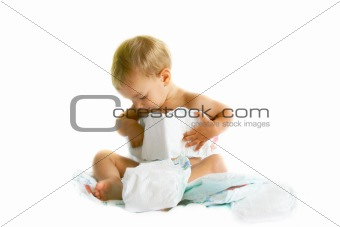 baby playing with diapers over white