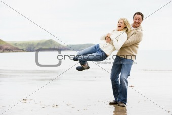 Couple playing on beach smiling