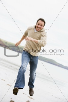 Man running on beach smiling