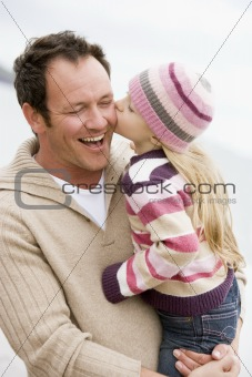 Father holding daughter kissing him at beach smiling