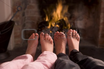 Children's feet warming at a fireplace