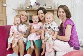 Three mothers in living room with babies smiling