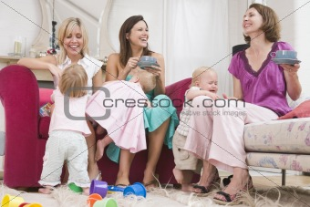 Three mothers in living room with coffee and babies smiling