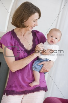 Mother in living room holding baby smiling