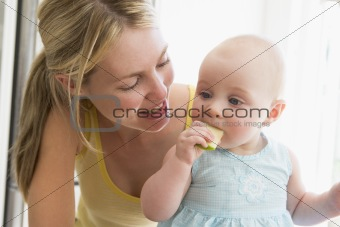Mother and baby in kitchen eating apple