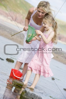 Mother and daughter at beach fishing and smiling