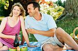 Couple sitting outdoors with picnic smiling
