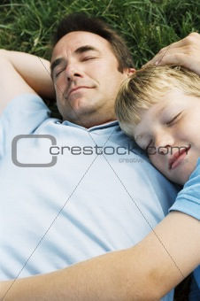 Father and son lying outdoors sleeping