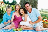 Family sitting outdoors with picnic smiling