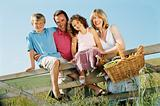Family outdoors by fence with picnic basket smiling